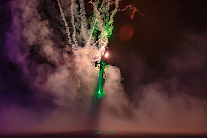 A low-wing rc aerobatic plane vertically climbs into a fireworks display.